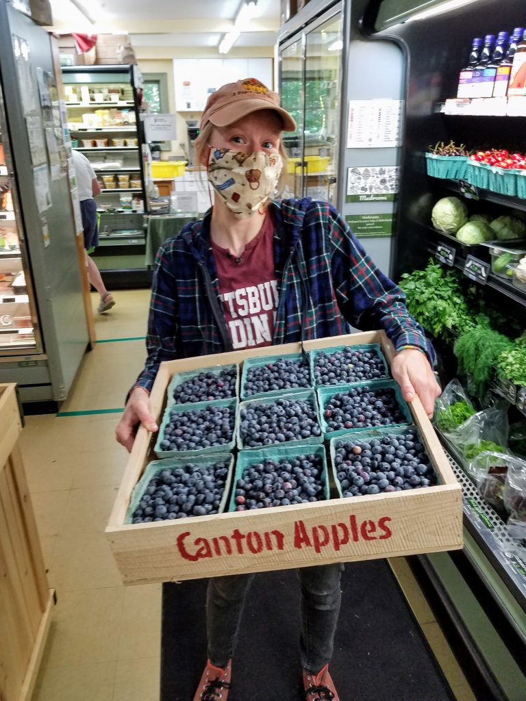 Allyssa holding shipment of blueberries - you too can work at the Co-op
